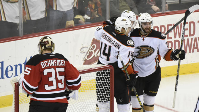 Anaheim Ducks' Tomas Fleischmann(14), Ryan Kesler (17) and Kyle Palmieri (21) celebrate a goal by Francois Beauchemin as New Jersey Devils goaltender Cory Schneider reacts during the third period of an NHL hockey game Sunday, March 29, 2015, in Newark, N.J. The Ducks won 2-1. (AP Photo/Bill Kostroun)