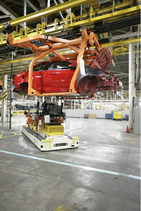 In this April 25, 2012 photo, a drive train assembly moves in to be mated with a Chevrolet Sonic at the Orion Assembly plant in Orion Township, Mich. Nearly four years after GM filed for bankruptcy pr