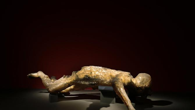 A cast of a woman, one of more than 70 people who died in the basement of a villa in Oplontis, near Pompeii, is seen during a photo call for the upcoming exhibition entitled 'Life and death Pompeii and Herculaneum', at the British Museum in central London, Tuesday, March 26, 2013. The void her body left in the ash was filled with clear epoxy resin, and he resulting cast reveals her skeleton and the jewelry she was wearing. The exhibition about the two Roman cities, buried by a catastrophic volcanic eruption of Mount Vezuvius in 79 AD, will run at the museum from March 28 to Sept. 29, 2013. (AP Photo/Lefteris Pitarakis)