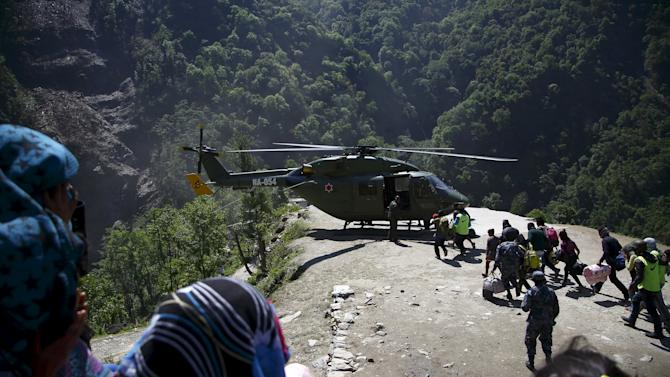 Earthquake victims run towards an helicopter to get airlifted to Kathmandu after last week's earthquake at Sindhupalchok District
