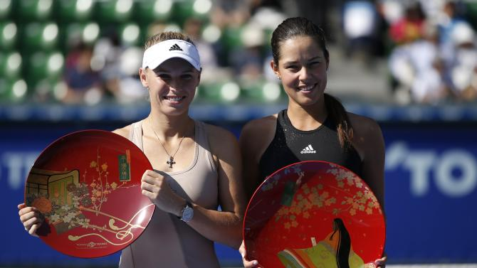 Ivanovic of Serbia and Wozniacki of Denmark pose with their trophies during an award ceremony after their Pan Pacific Open women's singles final tennis match in Tokyo