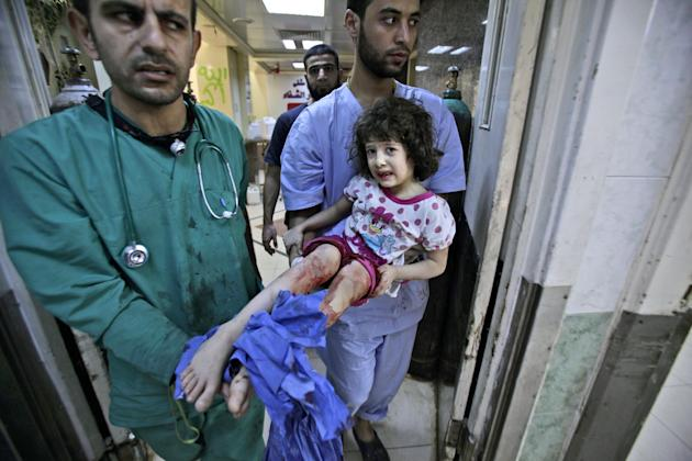 Medics carry Fatima Qassem, 6, whose legs were badly injured when government forces fired on her family's car, into the emergency room in a hospital in Aleppo, Syria, Tuesday, Sept. 11, 2012. (AP Phot