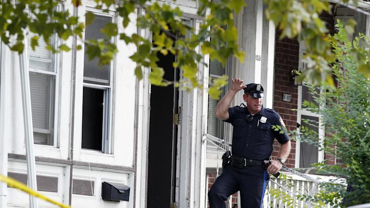 "A police officer stands at the doorway of 1415 Kaighn Ave., in Camden, N.J., Wednesday, Aug. 22, 2012, after police in Camden say a 2-year-old boy was decapitated, apparently by his mother, and his head left in the freezer of their home before woman fatally stabbed herself. Chevonne Thomas, 33, called 911 just after midnight to say something had happened to her child and it ""sounded like she had done it,"" Camden County Prosecutor's Office spokesman Jason Laughlin said. Officers found Zahree Thomas' body on the first floor of the home and the boy's head in the freezer. (Photo/Mel Evans)"