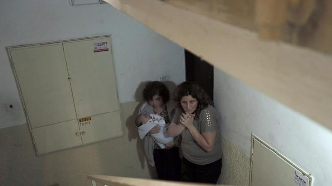 Israeli women take cover in a stairwell  as a siren signals the warning of incoming rockets in the coastal city of Ashkelon, Monday, Nov. 19, 2012. Israeli aircraft struck crowded areas in the Gaza Strip and killed a senior militant with a missile strike on a media center Monday, driving up the Palestinian death toll to 96, as Israel broadened its targets in the 6-day-old offensive meant to quell Hamas rocket fire on Israel. (AP Photo/Tsafrir Abayov)