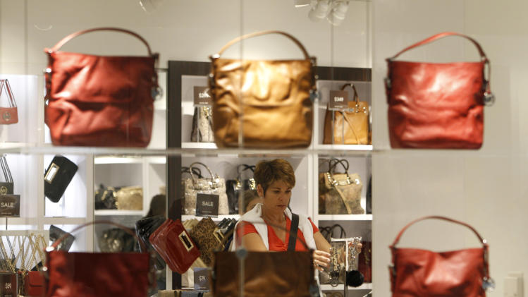 FILE - In this Nov. 9, 2011, file photo, a tourist from Switzerland, looks at jewelry at a Michael Kors store while shopping at Dolphin Mall, in Miami. The economy's recovery looks durable. Hiring, housing, consumer spending and manufacturing all look better but remain less than healthy. (AP Photo/Lynne Sladky, File)