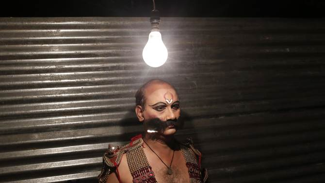 An artist dressed as a demon waits to get ready backstage before performing during Ramlila in New Delhi