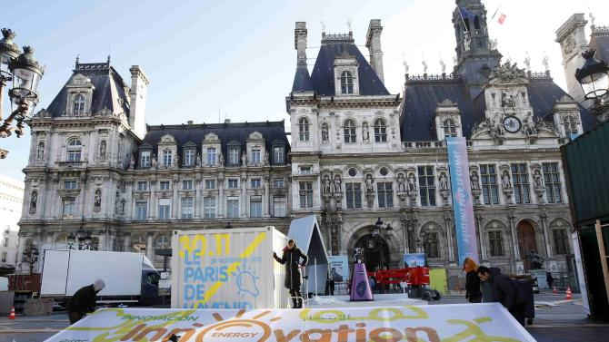 """Employees put the final touches during the installation of the exhibition """"Paris de L'Avenir"""", a showcase for tangible climate solutions, in front of Paris city hall"""