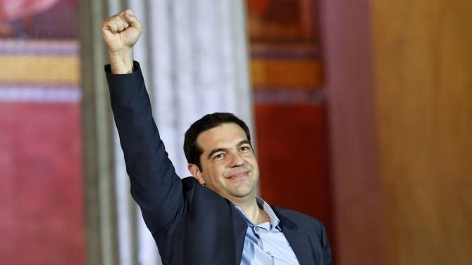 The head of radical leftist Syriza party Tsipras raises his fist to supporters after winning the elections in Athens