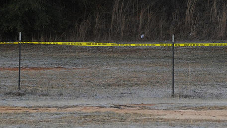 A police officer ropes off an area on site at the property of Jimmy Lee Sykes, a suspect accused of holding a 5-year-old boy hostage in an underground bunker on Saturday Feb.  2, 2013 in Midland City, Ala. Negotiators were still trying to persuade Jimmy Lee Dykes to surrender. Police have said they believe the Lee Dykes, a Vietnam-era veteran,  fatally shot a school bus driver Tuesday, and then abducted the boy from the bus and disappeared into the home-made bunker.  (AP Photo/al.com, Joe Songer)