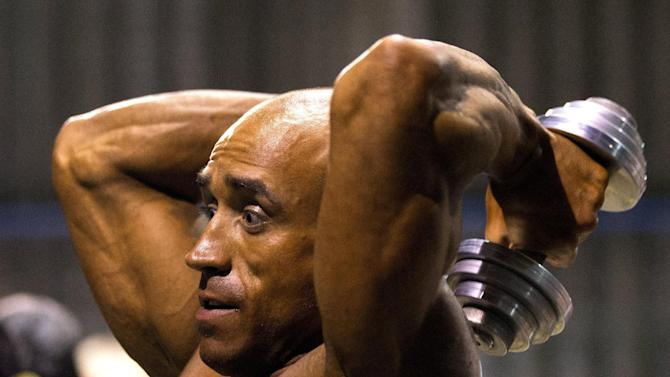 Participant does exercises backstage during Belarus bodybuilding and fitness championship in Minsk