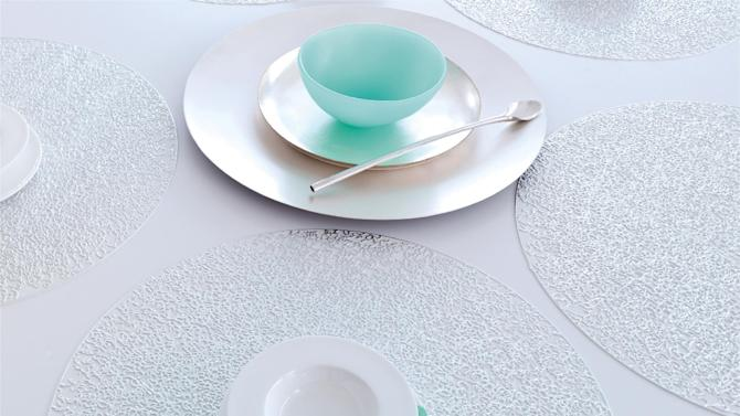 This undated publicity photo provided by Chilewich shows pressed filigree silver-white placemats. Sandy Chilewich's finely embossed ornamental design is created with a one of a kind mold and is spot printed with metallic foil to suggest the weathered look of a delicate old textile, although the mat itself is durable vinyl (www.chilewich.com).  (AP Photo/Chilewich, Victor Schrager Photography)
