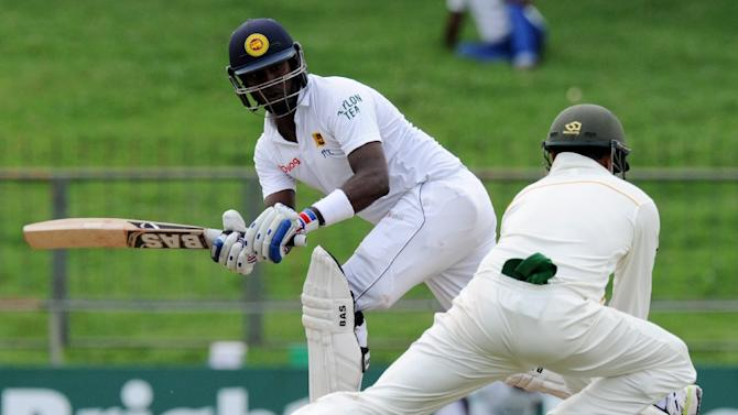 Sri Lanka captain Angelo Mathews (L) plays a shot as Pakistan cricketer Azhar Ali (L) fields during the third day of the third and final Test at the Pallekele International Cricket Stadium in Pallekele on July 5, 2015