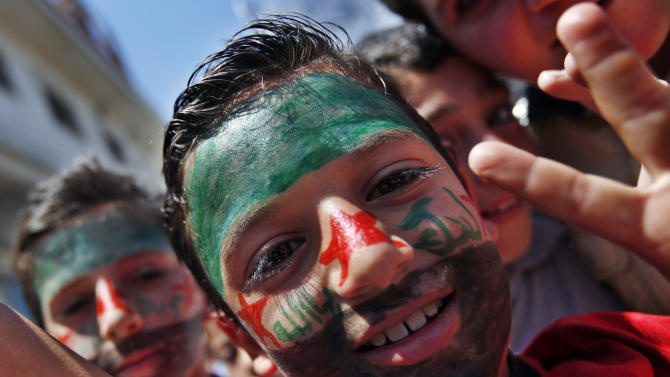 Syrian boys wearing face paint in the colors of the revolutionary flag attend an anti-Bashar Assad protest after Friday prayers on the outskirts of Idlib, Syria, Friday, June 8, 2012.  (AP Photo)