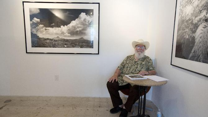 In this Saturday, June 27, 2015 photo, photographer Clyde Butcher sits in his Miami studio. Butcher's black-and-white landscape images have been infused with a new sense of freedom since the Florida-based photographer switched to a digital camera last year. (AP Photo/J Pat Carter)