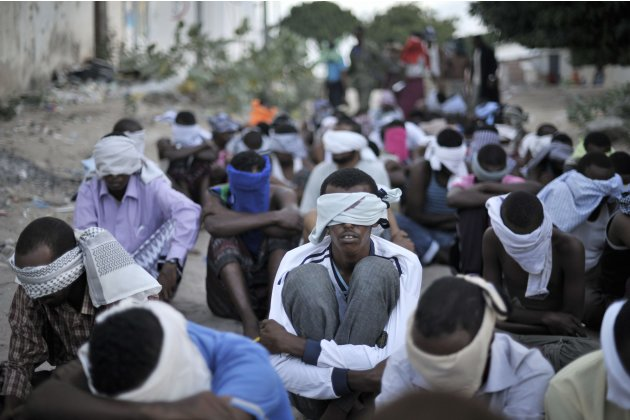 Men sit blindfolded after being rounded up by the Somali Police Force, to be screened during an operation aimed at improving security in Mogadishu
