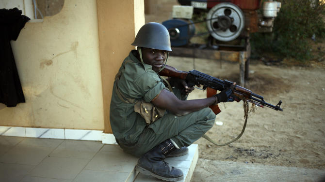 A Malian soldier takes cover behind a wall during exchanges of fire with jihadists in Gao, northern Mali, Sunday, Feb. 10, 2013. (AP Photo/Jerome Delay)