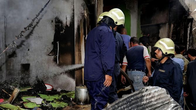 In this photo released by the Syrian official news agency SANA, firefighters investigate damages after two suicide bombings hit security compounds in Damascus, Syria, Wednesday, June 23, 2013. Syrian activists and state media say several have been killed in two suicide bombing attacks on security compounds in the capital, Damascus. The state-run news agency says three suicide bombers blew themselves up while trying to break into the Rukneddine police station. (AP Photo/SANA)