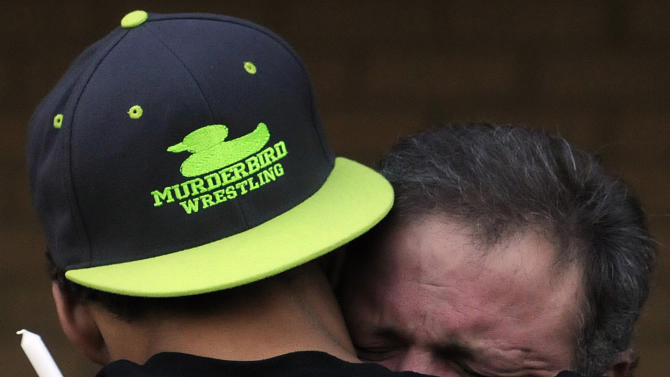 Marcus Graham, left, hugs Reed Collar, father of former Wetupmka student and wrester Gilbert Collar, at a vigil on Tuesday, Oct. 9, 2012, at the high school in Wetumpka, Ala. Collar was shot and killed by a University of South Alabama police officer on Oct. 6. (AP Photo/Montgomery Advertiser, Amanda Sowards)