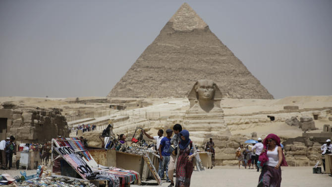 """In this photo taken Friday, May 31, 2013, tourists walk past vendors at the Giza Pyramids in Giza, Egypt. A statement by Egypt's Antiquities' Ministry Saturday, June 1, 2013 says a U.S. Embassy security warning sent to citizens to be extra cautious for their safety in the area of the Pyramids is baseless. Earlier in the week, the U.S. Embassy in Cairo sent a message to its citizens warning them to """"elevate their situational awareness when traveling to the Pyramids"""" due to a """"lack of visible security or police"""" in the area. (AP Photo/Hiro Komae)"""
