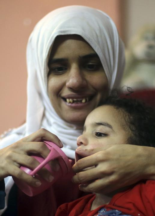 Sherien Fathy, a blind 32-year-old mother of two, feeds her daughter Rahma at her home in Cairo