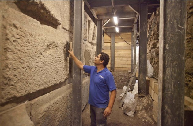 In this picture taken Tuesday, Aug. 2, 2011, Eli Shukron, an Israel Antiquities Authority archaeologist cleans stones making part of an underground section of the Western Wall at the end of what archa