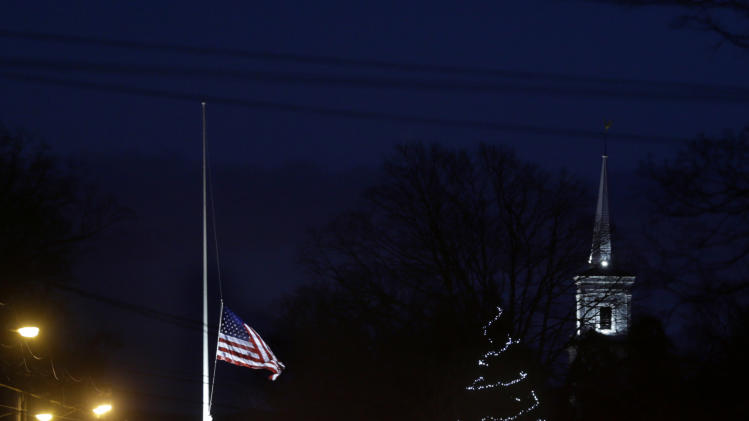 FILE - In this Thursday, Dec. 20, 2012 file photo, under a flag at half-staff and a Christmas tree, traffic piles up along a main road in Newtown, Conn. In the wake of the shooting, the grieving town is trying to find meaning in Christmas. (AP Photo/Seth Wenig, File)