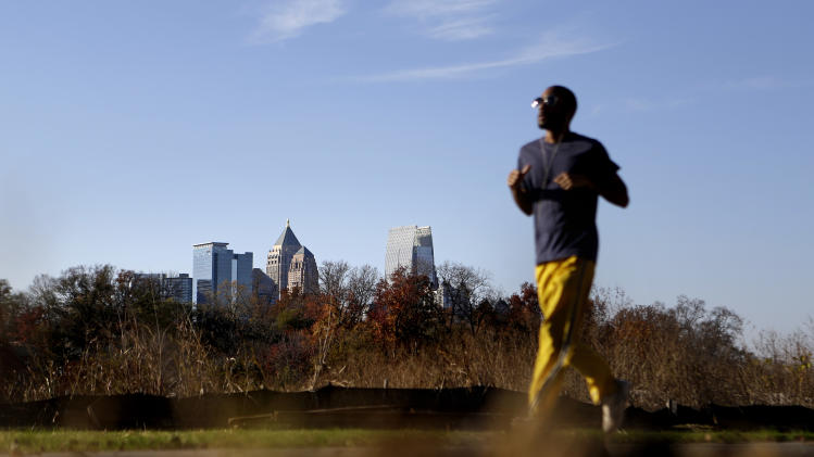 In this Nov. 20, 2012 photo, a jogger runs along the Atlanta BeltLine as midtown high-rises stand in the background in Atlanta. Since an Atlanta nonprofit opened a 2.25-mile-long paved trail east of downtown last month, it has attracted a steady stream of joggers, dog-walkers and cyclists to take in spectacular views of the skyline as well as a slice of established neighborhoods that were once only seen by riding a freight train. The Eastside Trail is the latest and most visible phase of the Atlanta BeltLine, an ambitious $2.8 billion plan to transform a 22-mile railroad corridor that encircles Atlanta into a network of parks, trails, public art, affordable homes and ultimately streetcars. (AP Photo/David Goldman)