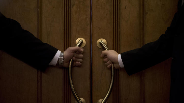AP10ThingsToSee - Hotel security officers guard at an entrance door of a hotel room set aside for relatives or friends of passengers aboard a missing Malaysia Airlines plane, in Beijing, China Wednesday, March 12, 2014. (AP Photo/Andy Wong)