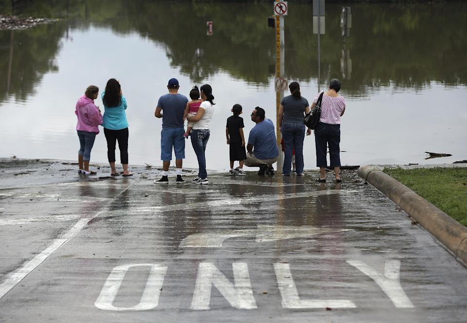 Onlookers gather along a flooded intersection, Sunday, May 26, 2013, in San Antonio. Heavy rains and flooding are being blamed for at least two deaths in San Antonio. (AP Photo/Eric Gay)