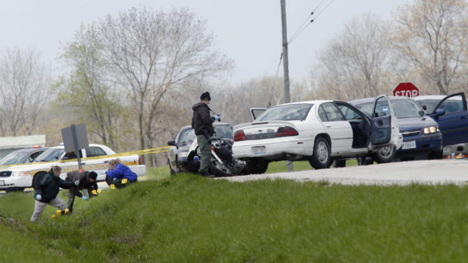 Illinois State Police process the scene Wednesday, April 24, 2013, near Winchester, Ill., where a suspect that was wanted in the deaths of five people in nearby Manchester, Ill., was wounded after a car chase and an exchange of gunfire with law enforcement. The suspect, who was driving the white sedan, died later at a hospital. (AP Photo/The State Journal-Register, Ted Schurter)