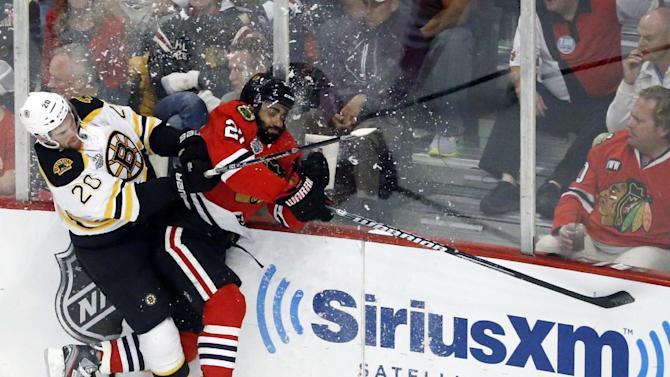 Boston Bruins left wing Daniel Paille (20) and Chicago Blackhawks defenseman Johnny Oduya (27) collide during the first period of Game 1 in their NHL Stanley Cup Final hockey series on Wednesday, June 12, 2013, in Chicago. (AP Photo/Charles Rex Arbogast)