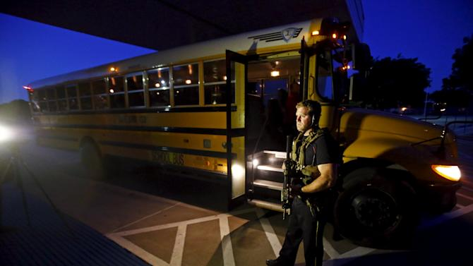 A police officer stands near a school bus used to evacuate attendees of the Muhammad Art Exhibit and Contest after a shooting, in Garland, Texas