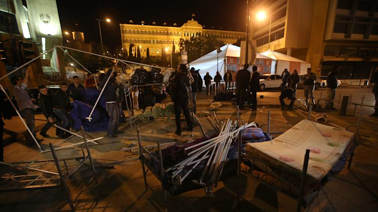 Lebanese anti-government protesters dismantle their tents which were set as an open sit-in since 5 months ago in front the government palace, seen in the background, after the Lebanese Prime Minister Najib Mikati announced his resignation, in Beirut, Lebanon, Friday march 22, 2013. Lebanon's prime minister resigned Friday due to government infighting that threatens to leave a void in the state's highest ranks at a time of rising tensions and sporadic violence enflamed by the civil war in neighboring Syria.(AP Photo/Hussein Malla)