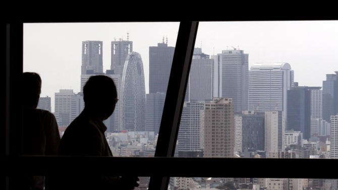 In this Sept. 6, 2013 photo, people look at Tokyo's high-rise buildings. Japan's economy expanded faster in April-June than earlier reported, according to a revised estimate showing a real annualized growth rate of 3.8 percent, thanks to higher spending on private and public investment. The Cabinet Office also said Monday, Sept. 9, that the economy expanded 0.9 percent from the previous quarter, compared with an earlier estimate of a 0.6 percent increase. (AP Photo/Shuji Kajiyama)