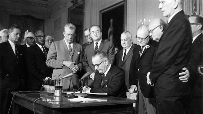 FILE - This July 2, 1964 file photo shows President Lyndon Baines Johnson signing the Civil Rights Act in the East Room of the White House in Washington. Standing, from left, are Sen. Everett Dirksen, R-Ill.; Rep. Clarence Brown, R-Ohio; Sen. Hubert Humphrey, D-Minn.; Rep. Charles Halleck, R-Ind.; Rep. William McCullough, R-Ohio; and Rep. Emanuel Celler, D-N.Y. The Civil Rights Act of 1964 is considered one of the most celebrated legislative achievements in U.S. history. Signed on July 2, 1964 by President Lyndon B. Johnson, this law made it illegal to discriminate on the basis of race, color, religion, sex, or national origin, and barred unequal application of voter registration requirements. (AP Photo, File)