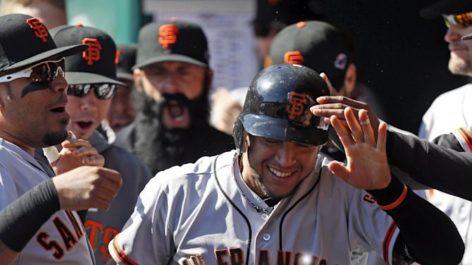 San Francisco Giants' Gregor Blanco, right, is congratulated in the dugout after scoring the first run of the game in the fifth inning of Game 5 of the National League division baseball series against the Cincinnati Reds, Thursday, Oct. 11, 2012, in Cincinnati. Blanco scored from first on an RBI triple by Brandon Crawford. (AP Photo/David Kohl)