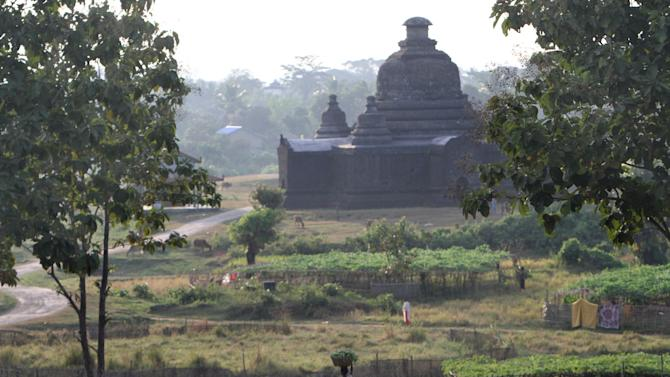 In this photo taken on Nov. 8, 2012, A woman walks in the foreground of a moss-covered ancient pagoda in Mrauk-U, Rakhine state, western Myanmar. Mrauk-U itself has been spared the bloodshed between the Buddhist Rakhine and the Muslim Rohingya that has scarred other parts of Rakhine state. It is calm, and for foreign tourists, safe. But just 10 kilometers (six miles) to the south, there is a village where civilians were reportedly beheaded in a massacre last month that saw women and children slaughtered, then buried in mass graves. Across western Myanmar's Rakhine state, the United Nations is distributing emergency supplies of food and shelter to terrified villagers who have fled burning homes. A nighttime curfew is in force. (AP Photo/Khin Maung Win)