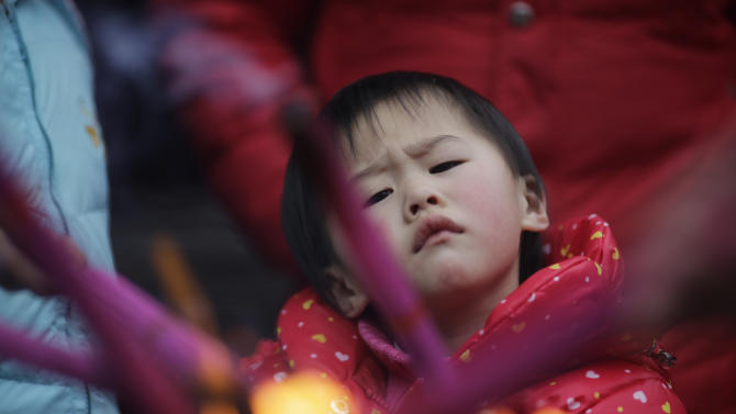 A child tries to light joss sticks at a temple in Shanghai, China on Monday Feb. 11, 2013, on the second day of the Chinese Lunar New Year. Chinese celebrate the arrival of the Year of the Snake, according to the Chinese Zodiac. (AP Photo/Eugene Hoshiko)