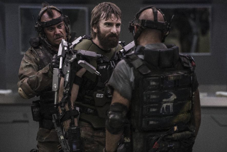 "This film publicity image released by TriStar, Columbia Pictures-Sony shows Sharlto Copley, center, in a scene from ""Elysium."" (AP Photo/TriStar, Columbia Pictures - Sony, Kimberley French)"