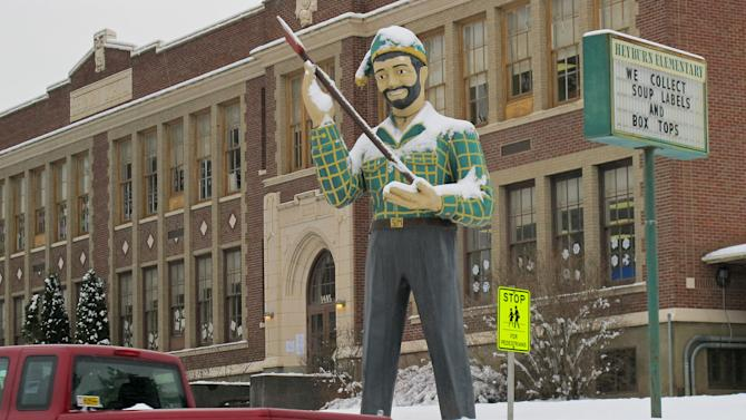 In this photo taken Jan. 15, 2013, a statue of a logger stands outside an elementary school in St. Maries, Idaho near where a survivalist group plans to build a compound. The proposal is called the Citadel and has created a buzz among folks in this remote logging town 70 miles southeast of Spokane, Wash. The project would more than double the population of Benewah County, home to 9,000 souls. (AP Photo/Nicholas K. Geranios).