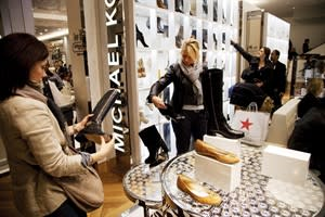 In this photo of Friday, Oct. 12, 2012, women shop in the Michael Kors section of Macy's shoe department in New York. The consumer price index rose a seasonally adjusted 0.1 percent in October, down from sharp gains of 0.6 percent in the previous two months, the Labor Department said Thursday. In the past year, prices increased 2.2 percent. That's just above the Federal Reserve's inflation target of 2 percent. (AP Photo/Mark Lennihan)