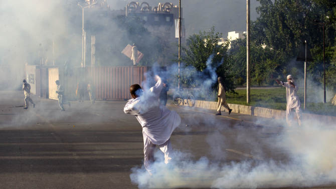 A Pakistani protester tosses a tear gas canister back at police behind containers blocking the road to the diplomatic enclave in Islamabad, Pakistan, Friday, Sept. 21, 2012. Pakistani police opened fire on rioters who were torching a cinema during a protest against an anti-Islam film Friday, and security forces clashed with demonstrators in several other cities in Pakistan on a holiday declared by the government so people could rally against the video. Thousands of people protested in several other countries, some of them burning American flags and effigies of President Barack Obama. (AP Photo/B.K. Bangash)
