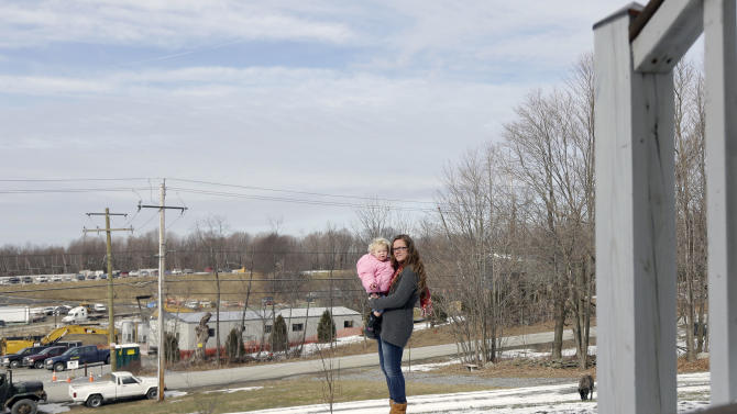 In this Thursday, Feb. 7, 2013 photo, Leanne Baum holds her daughter Hannah outside their home in Minisink, N.Y. The construction site for a natural gas compressor station is across the road from the house. (AP Photo/Mike Groll)