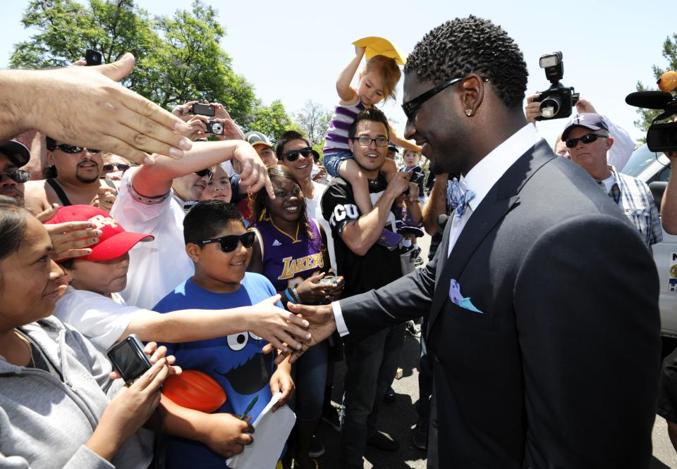 Former San Diego Chargers running back LaDainian Tomlinson shakes hands with fans after a news conference held at the San Diego Chargers facility Monday, June 18, 2012 in San Diego. Tomlinson signed a one-day contract with the Chargers and announced his retirement.   (AP Photo/Denis Poroy)