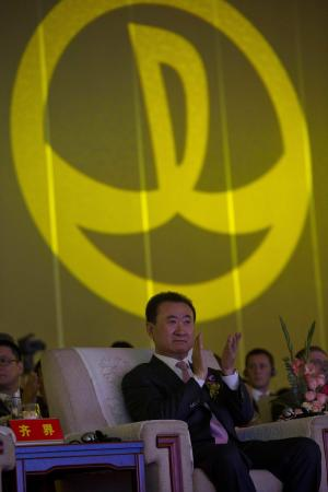 Wanda Chairman Wang Jianlin applauds in front of the logo for Dalian Wanda Group during an event at a hotel in Beijing, China, Wednesday, June 19, 2013. Chinese property and cinema conglomerate Dalian Wanda Group said it is buying British yacht maker Sunseeker and will develop an upmarket London hotel, expanding into the luxury market as part of the latest foray abroad by a major Chinese firm. (AP Photo/Ng Han Guan)