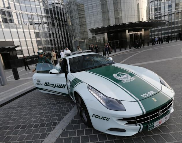 An Emirati female police officer gets out of a Lamborghini police vehicle on April 25, 2013 in the Gulf emirate of Dubai. Dubai police showed off a new Ferrari they will use to patrol the city state,