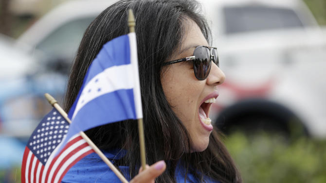 Brenda Betancourt holds American and Honduran flags as she chants during an immigration demonstration, in Doral, Fla., Wednesday, May 1, 2013. Demonstrators demanded an overhaul of immigration laws Wednesday in an annual, nationwide ritual that carried a special sense of urgency as Congress considers sweeping legislation that would bring many of the estimated 11 million people living in the U.S. illegally out of the shadows. (AP Photo/Wilfredo Lee)