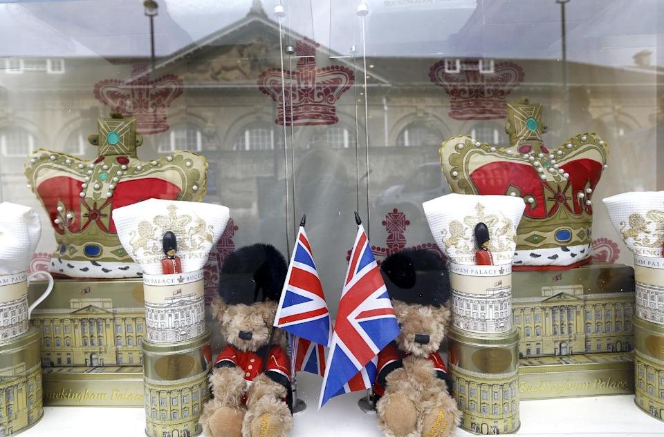 Buckingham Palace is reflected in the window of a souvenir shop selling teddy bears in London, Wednesday, July 24, 2013. Sales of royal related souvenirs are expected to rise after Britain's Duchess of Cambridge gave birth to a baby boy who will be third in line to the throne. (AP Photo/Kirsty Wigglesworth)