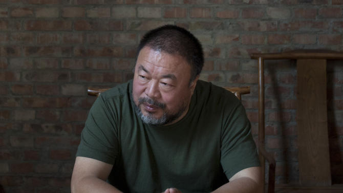"""FILE - In this May 22, 2013 file photo, Chinese artist Ai Weiwei speaks to journalists at his studio in Beijing, China, Wednesday, May 22, 2013. On the second anniversary of his 81-day secret detention, Ai is releasing his first music album """"The Divine Comedy,"""" which includes the single """"Dumbass."""" The full album, released Saturday, June 22, 2013, has five other songs, in which Ai documents his experiences with police and shares his reflection on China's current conditions.(AP Photo/Alexander F. Yuan, File)"""
