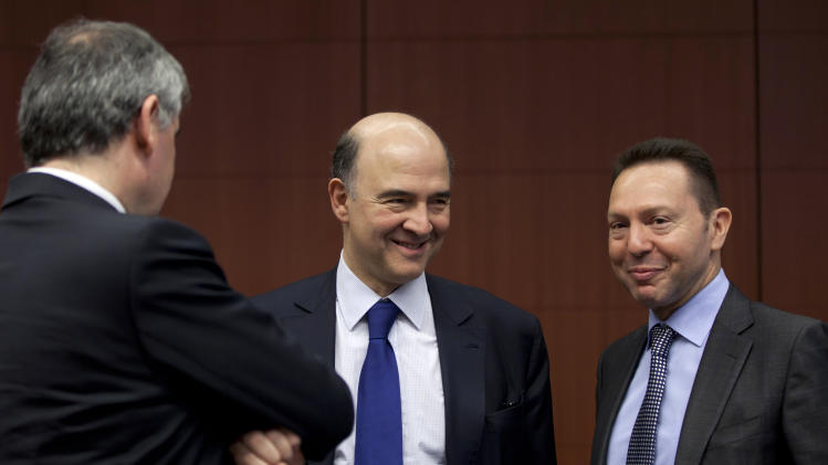 Greek Finance Minister Yannis Stournaras, right, speaks with French Finance Minister Pierre Moscovici during a meeting of  eurogroup finance ministers in Brussels on Monday, March 4, 2013. The eurogroup finance ministers are set to discuss details of a bailout for cash-strapped Cyprus, further steps of assistance for Portugal and Ireland as well as the controversial issue of direct banking recapitalizations through Europe's permanent rescue fund. (AP Photo/Virginia Mayo)